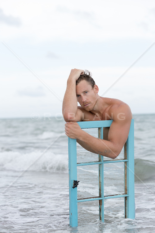 sexy man in the ocean with a mirror