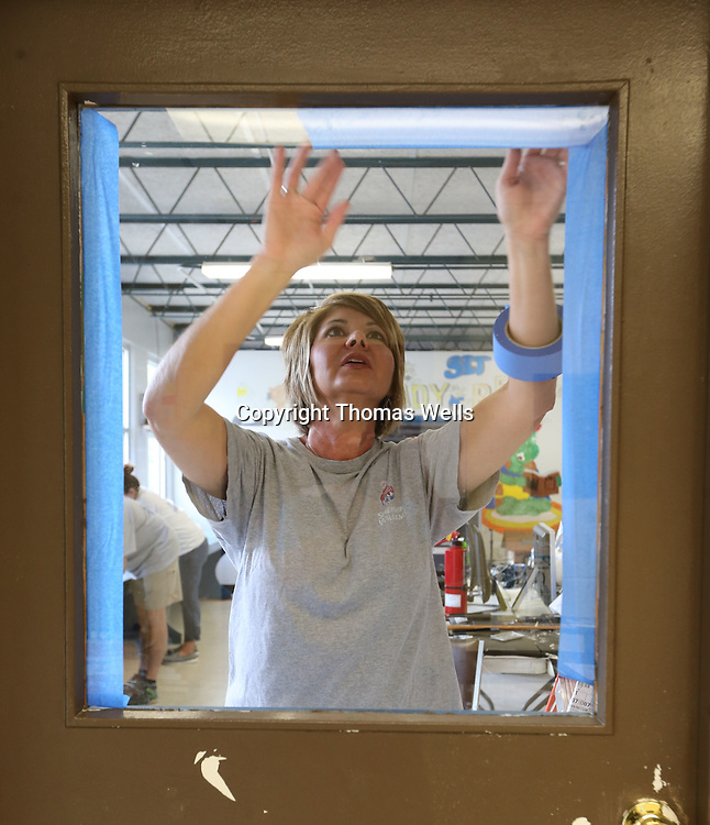 Kim Goodwin works on taping off the window to a door before it can be painted as volunteers spend their Thursday painting the interior of the Boys and Girls Club on North Green Street in Tupelo.