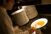 "Using a cloth, a waiter picks up a hot bowl of Butter Squash soup ready for a la carte service in the kitchens at the Vivre restaurant in Sofitel, a 605 bedroom, 27 suite and 45 meeting room accommodation and business hub Heathrow Airport's hub hotel attached to Terminal 5. A stack of clean and unused plates are ready for use on the hot plate that warms them  and we see the waiter leaning over in shadow, carefully taking hold of the bowl so that none of the liquid spills. The man is wearing a smart white shirt and is about to take the dish over to the customer's table. From writer Alain de Botton's book project ""A Week at the Airport: A Heathrow Diary"" (2009). ."