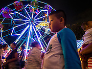 16 NOVEMBER 2013 - BANGKOK, THAILAND:  A Ferris wheel on the midway at the Wat Saket temple fair. Wat Saket is on a man-made hill in the historic section of Bangkok. The temple has golden spire that is 260 feet high which was the highest point in Bangkok for more than 100 years. The temple construction began in the 1800s in the reign of King Rama III and was completed in the reign of King Rama IV. The annual temple fair is held on the 12th lunar month, for nine days around the November full moon. During the fair a red cloth (reminiscent of a monk's robe) is placed around the Golden Mount while the temple grounds hosts Thai traditional theatre, food stalls and traditional shows.   PHOTO BY JACK KURTZ