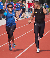 West Point, New York -  Army's Michael Kacer, right, encourages Tatiana Perkins of the Air Force near the finish line of the 200-meters at the 2014 Army Warrior Trials at the United States Military Academy Preparatory School on Tuesday, June 17, 2014.<br />