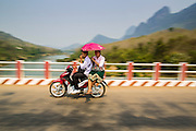 15 MARCH 2013 - BAN SOMSANOUK, LAOS: A couple on a motorcycle cross a bridge over the Nam Ou River in Ban Somsanouk near Luang Prabang, Laos.   PHOTO BY JACK KURTZ