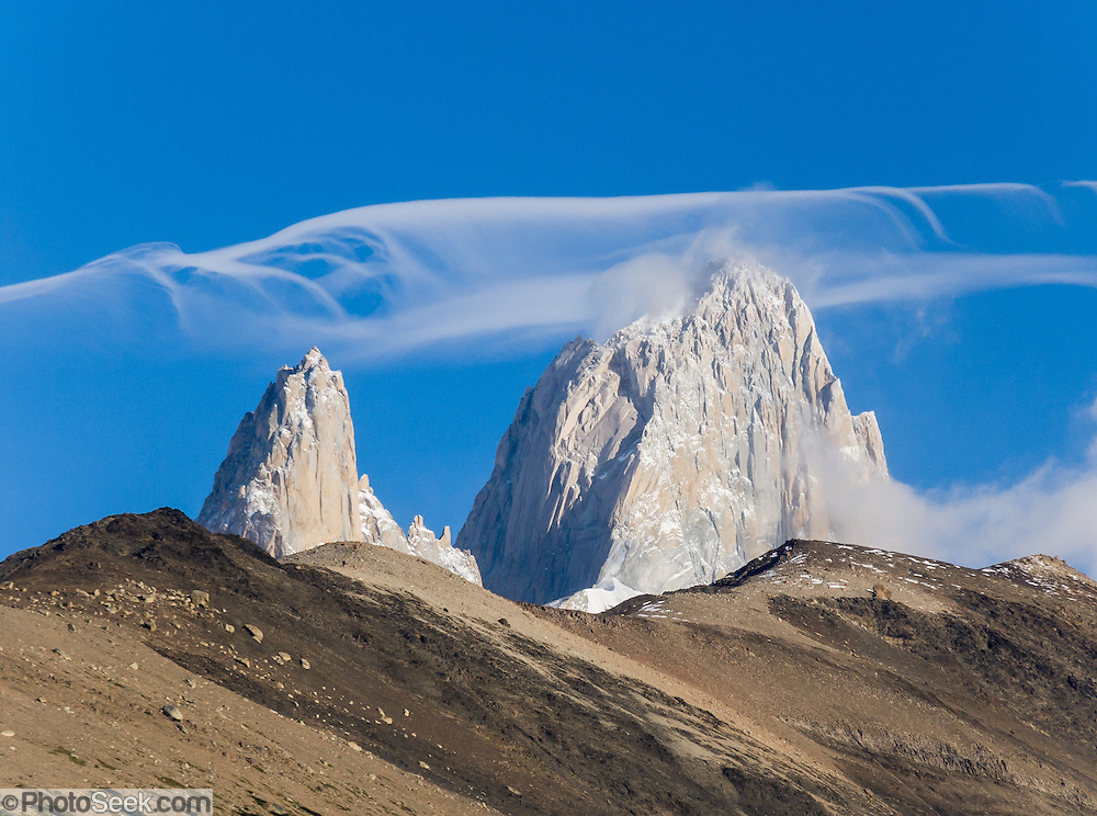 "High winds drive wave clouds over Mount Fitz Roy (3405 meters or 11,170 feet) in the Andes mountains, in Los Glaciares National Park, near El Chaltén village, Argentina, Patagonia, South America. Native Tehuelche (Aonikenk) people called this mountain (and others) Chaltén, meaning ""smoking mountain,"" which is understandable from the frequent orographic clouds. The atmospheric internal waves that form wave clouds are created as stable air flows over a mountain creating an oscillation of uplift and descent. Clouds can form from invisible water vapor turning into white droplets at the cooled crests of internal waves and evaporate (due to adiabatic heating) as the wave descends. First climbed in 1952 by French alpinists Lionel Terray and Guido Magnone, Mount Fitz Roy has very fickle weather and is one of the world's most challenging technical ascents. It is also called Cerro Chaltén, Cerro Fitz Roy, and Monte Fitz Roy (with a space before the R). Cerro is a Spanish word meaning hill. In 1877, explorer Perito Moreno named ""Cerro Fitz Roy"" for Robert FitzRoy (no space before the capital R) who, as captain of the HMS Beagle, had travelled up the Santa Cruz River in 1834 and charted much of the Patagonian coast. Spanning both Argentina and Chile, the foot of South America is known as Patagonia, a name derived from coastal giants (""Patagão"" or ""Patagoni"" who were actually Tehuelche native people who averaged 25 cm taller than the Spaniards) who were reported by Magellan's 1520s voyage circumnavigating the world. The Patagonia company based their clothing logo on the shape of Mount Fitz Roy, after Yvon Chouinard's ascent and subsequent film in 1968. The town of El Chaltén was built in 1985 by Argentina to help secure the disputed border with Chile. The nearest airport is 220 km south at El Calafate."
