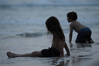 Children play on the beach at sundown.