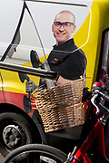 A smiling man from the repair service Autoglass seen fitting a new car windscreen on the side of the company van, and a bicycle basket, on 30th January 2018, in the south London borough of Southwark, England.
