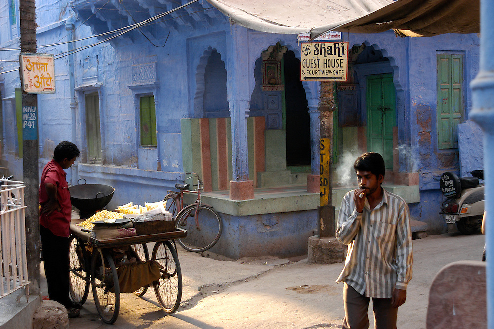 Sreetscene in the blue city of Jodhpur, Rajasthan (India) where a street vendor is preparing puffed rice while a smoking man passes by.