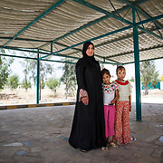 Salsabeel, 30, her three children, and her husband fled Syria. After their home was destroyed, they had nothing left. Salsabeel&rsquo;s children &mdash; her two girls and her son Hamza, 3, are everything she has now.<br /> <br /> She and her daughters Bayal and Nada are standing under a community garden cover that was built to help encourage Jordanians and Syrians to socialize with oneanother. Sahal Huron, Jordan, May 2015.