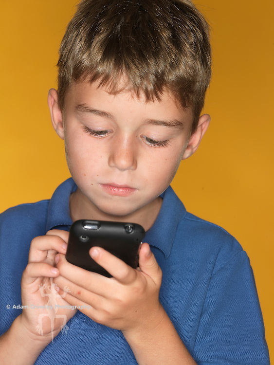 7 year old boy operates a mobile phone (iPhone)
