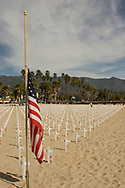 American flag at half mast next to crosses on a beach in Santa Barbara representing the fallen soldiers of the Irac and Afganistan wars.