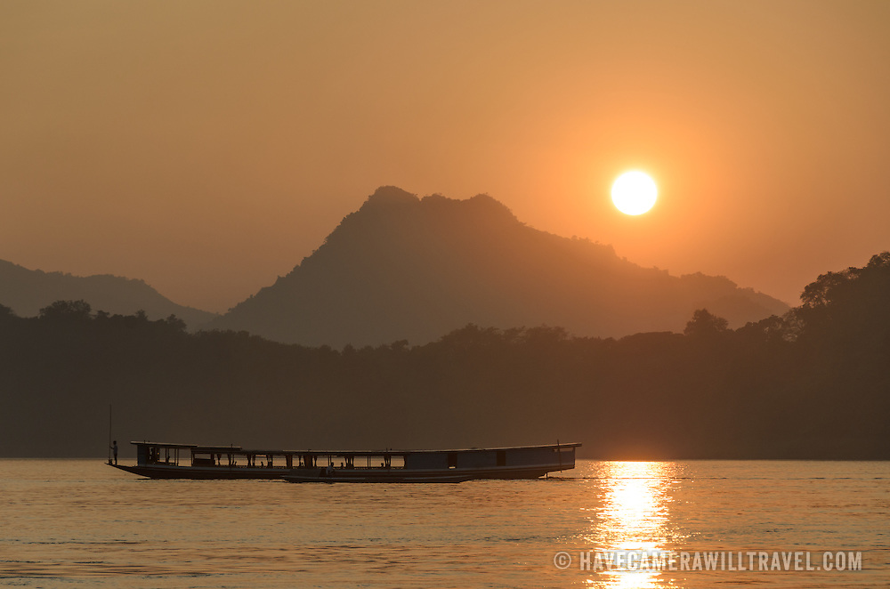Boats on the Mekong at sunset on the Mekong River near Luang Prabang, Laos.