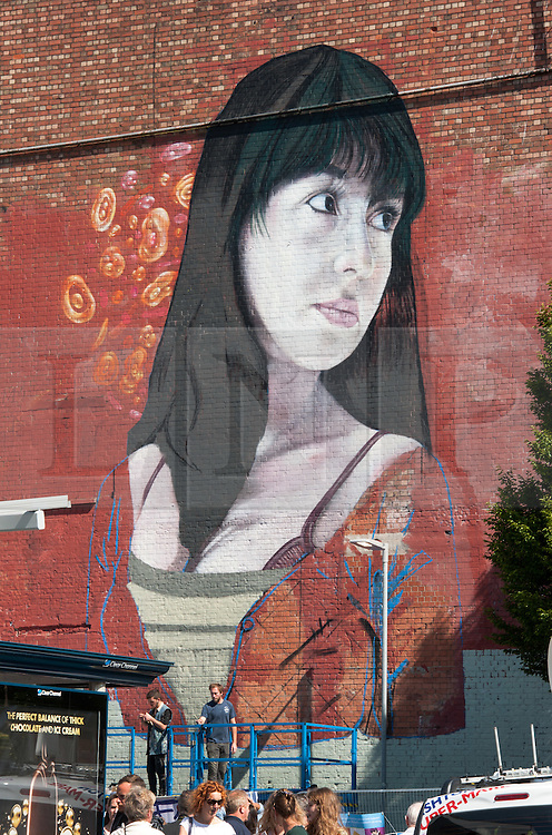 © Licensed to London News Pictures. 25/07/2015. Bristol, UK.  Giant mural of a girl's face by Martin Ron on the sides of the Tobacco Factory building at Upfest 2015, Europe's largest, free, street art & graffiti festival, attracting over 250 artists painting 28 venues throughout Bedminster & Southville, Bristol.  Talented artists travel from 25 countries and across the UK to paint live on 30,000sqft of surfaces in front of 25,000 visitors. There is also an affordable art sale, music stages and art workshops.  Photo credit : Simon Chapman/LNP