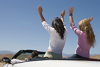 Man and two young women raising arms in car