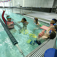 Holly Walker reminds her swim students the proper way for the back stroke as part of the spring break swim lesson at the Wellness Center Thursday.