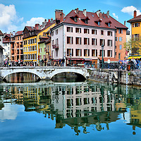 Pont Perrière over Thiou Canal in Annecy, France <br /> The Perrière Bridge is the first and most famous of the footbridges crossing the Thiou canal in Annecy, France. It connects the Quai de I'lle on the right with the Quai des Vielles Prisons on the left where you also catch a glimpse of Palais de I'Isle.