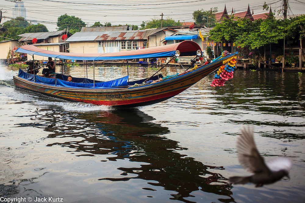 04 JANUARY 2012 - BANGKOK, THAILAND:  A pigeon takes off as a longtailed boat takes passengers up Khlong Phra Khanong past Wat Mahabut in eastern Bangkok. The temple was built in 1762 and predates the founding of the city of Bangkok. Just a few minutes from downtown Bangkok, the neighborhoods around Wat Mahabut are interlaced with canals and still resemble the Bangkok of 60 years ago. Wat Mahabut is a large temple off Sukhumvit Soi 77. The temple is the site of many shrines to Thai ghosts. Many fortune tellers also work on the temple's grounds.   PHOTO BY JACK KURTZ