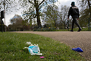 At the beginning of the second week of the UK's Coronavirus lockdown and in accordance with government guidelines for social distancing and local daily exercise, a used discaded surgical mask and glove lie in the grass alongside a passing Londoner in Ruskin Park, a green public space in the borough of Lambeth, south London, on 30th March 2020, in London.