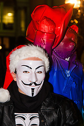 "London, December 23rd 2014. Online activism group Anonymous march through London from the City to the BBC's HQ on Great Portland Street in protest against alleged biases and coverups of a ""paedophile ring"". PICTURED: Paddington Bear poses with a protester in his Guido Fawkes mask."