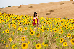 © Licensed to London News Pictures. 08/08/2020. CHORLEYWOOD, UK. A woman stands amongst the sunflowers growing in a wheat field near Chorleywood, Hertfordshire on a hot day where the temperature is expected to peak at 34C.  The forecast is for temperatures to continue to exceed 30C for the next few days.  Photo credit: Stephen Chung/LNP