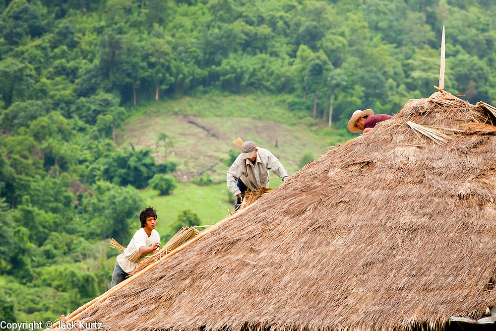 27 JUNE 2011 - CHIANG MAI, THAILAND: Workers finish a thatched roof of a structure north of Chiang Mai, Thailand. Thatch is still used in construction in Thailand.  PHOTO BY JACK KURTZ