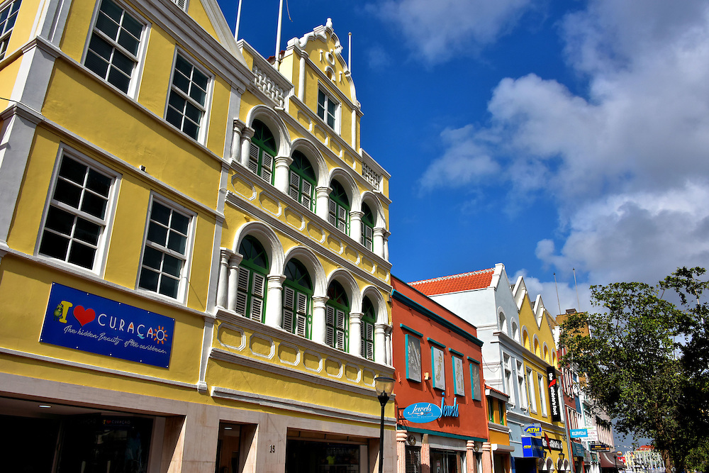 """Shopping Districts in Punda, Eastside of Willemstad, Curaçao  <br /> If you spell the word vacation as s-h-o-p-p-i-n-g, then you will agree with the sign """"I Love Curaçao."""" This is Breedestraat, one of the three main retail streets in Punda. The other two intersect it: Handelskade and Heerenstraat. Market stalls are located along Shailio Caprileskade on the Waaigat waterfront. The place to explore on the Otrobanda side is the 50 stores at Renaissance Mall. If you are interested in European items, then consider Saliña Galleries. These are just a few of your options. You will find other malls and boutique shops across the island.  Your credit card will get worn out before your feet do."""