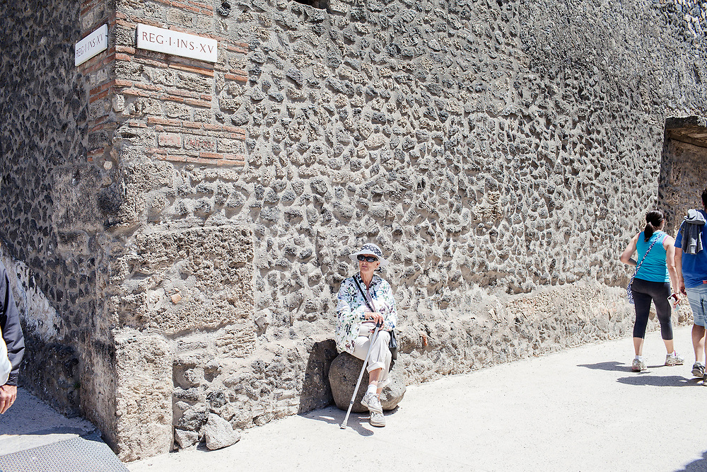 20 May 2017, Pompei, Naples Italy - 20 May 2017, Pompei, Naples Italy - A old visitor sit on the ruins of the ancient city of Pompeii.