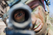 A Rifleman takes aim through the sight of his SA 80 rifle. The Rifles on live firing training in Northern Kenya.