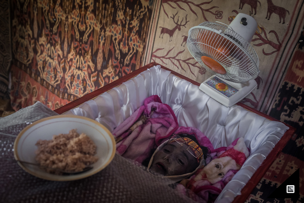 """""""Kumande Komi Mama"""" wake for lunch, Yari he addresses 'sick' mother and puts the bowl of rice as well as the ventilator in place. Ribka Tanduk Langi died 2 month ago in the age of 53 because of liver failure. Ribka Tanduk Langi left 8 children behind. Her second son Yari assumes it was hepatitis but it was too late for them to check in the city of Makassar which is 8 hours away from Tana Toraja. God call her to puya, her son tells me. They will soon schedule the funeral (Rambu solo), probably for june next year, because all the relatives are working overseas, it takes time to make them all come back. So they will wait for holiday time."""