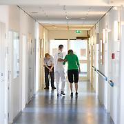 Nederland Rotterdam  31-08-2009 20090831 Foto: David Rozing .Serie over zorgsector, Ikazia Ziekenhuis Rotterdam. Afdeling neurologie, stroke unit,  revalidatie jonge vrouw en oude man. Broeder helpt en ondersteunt patient tijdens het oefenen/ leren van lopen, op de gang van de afdeling. De patient is deels verlamd, waardoor haar  ( grove ) motoriek is aangetast,  geraakt.  Revalidation young and old patient, nurse practice walking, supporting her while walking.  Patient is partly paralysed. .. - nb: oorzaak van ziektebeeld van deze 2 patienten is mij niet bekend - .Foto: David Rozing ....Holland, The Netherlands, dutch, Pays Bas, Europe, interactie patient verpleging, tijd hebben voor,  ,zorgaanbieder, zorgaanbieders, geneeskunde, ill, illness, behandelplan, genezing, genezen,  ziekte bestrijding bestrijden, real people, echte mensen, persoon, personen, oud, oude, op leeftijd, steun, steunen, helpen,  , revalidatie, revalideren, revalidation, nursing,aanmoedigen, hulp, helpen,onherkenbaar, onherkenbare, unrecognisable, mobiliteit, niet mobiel zijn, verlamd zijn, niet goed kunnen lopen,,handeling, handelingen, ondersteunen,zorgverlener, zorgverleners,zorgverlening, jong, jonge meid, oud en jong, ondersteuning