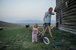 """Hilary Anderson plays with her daughter Elle outside their home on the J Bar L ranch. The J Bar L ranch is a unique, conservation-friendly ranch nestled into the wide open land of the Centennial Valley in southern Montana. The ranch finishes their cattle on grass, in contrast to the vast majority of ranches in the U.S. that send cattle to feedlots. The 2,000 head at J Bar L """"never go into a feedlot,"""" said Bryan Ulring, manager of the ranch. He added that J Bar L is one of the biggest grass finishers in the state. The Centennial Valley is an important wildlife corridor for elk, moose, antelope, deer, wolverines, grizzly bears, wolves and hundreds of bird species. The valley is largely owned by a handful of large ranches, which means their use of the land impacts the local environment. © Ami Vitale"""