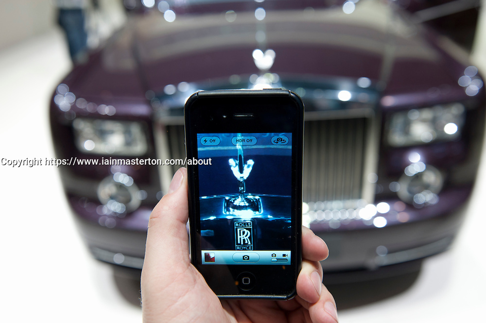 Visitor photographing Rolls-Royce car with phone camera at the Geneva Motor show 2011 Switzerland