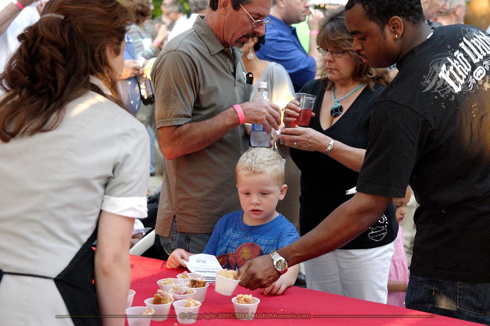 Folks gets samples from Culp's Cafe during the 21st annual The Taste in the Lincoln Park Commons area at the Fraze Pavilion, Thursday, September 3, 2009.