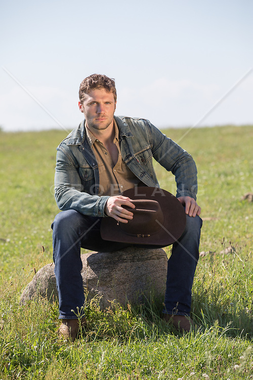 cowboy sitting on a rock