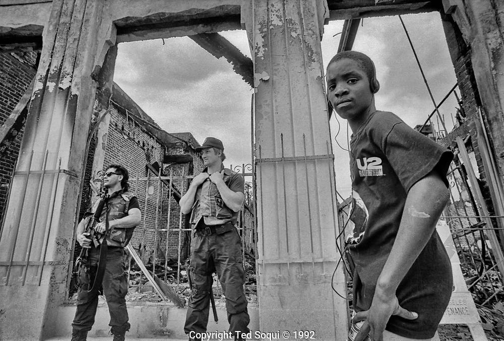 A kid wearing a U2 &quot;Rattle and Hum&quot; t-shirt listens to music on his headphones next two two heavily armed officers in front a building that was burned down during the LA92 riots.<br /> 1925 W. Adams Blvd.<br /> <br /> 25 before and after LA92 photo project.