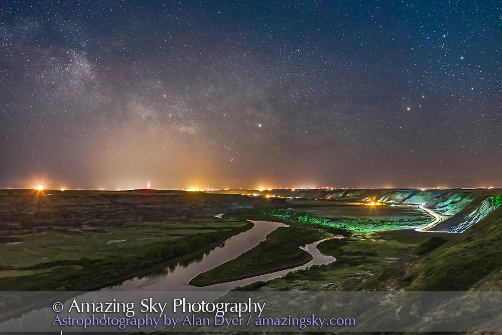 The Milky Way in Sagittarius and Scorpius to the south over the Red Deer River from Orkney Viewpoint, and competing with the urban skyglow from Drumheller washing out the sky. A car travelling to the south added the &ldquo;car trails&rdquo; and lit the valley. <br /> <br /> Antares and Scorpius are at right, Saturn is at centre, and Sagittarius is left of centre. <br /> <br /> This is a stack of 5 frames for the ground, and one for the sky, all tracked on the Star Adventurer Mini as a test of its Astro Time-Lapse mode which tracks the sky for each exposure then resets back to the starting point after each exposure. So the stars remain pinpoint but the ground is blurred somewhat. Each exposure was 45 seconds at f/2.8 and ISO 1250 with the 35mm lens and Canon 6D.