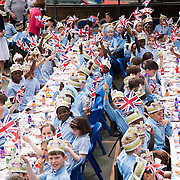 Children waving English flags to celebrate the Diamond Jubilee at Corpus Christi Catholic School. London 1st June 2012