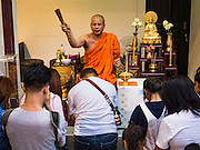 21 NOVEMBER 2015 - BANGKOK, THAILAND: A monk sprinkles holy water on people at the Wat Saket temple fair. Wat Saket is on a man-made hill in the historic section of Bangkok. The temple has golden spire that is 260 feet high which was the highest point in Bangkok for more than 100 years. The temple construction began in the 1800s in the reign of King Rama III and was completed in the reign of King Rama IV. The annual temple fair is held on the 12th lunar month, for nine days around the November full moon. During the fair a red cloth (reminiscent of a monk's robe) is placed around the Golden Mount while the temple grounds hosts Thai traditional theatre, food stalls and traditional shows.     PHOTO BY JACK KURTZ