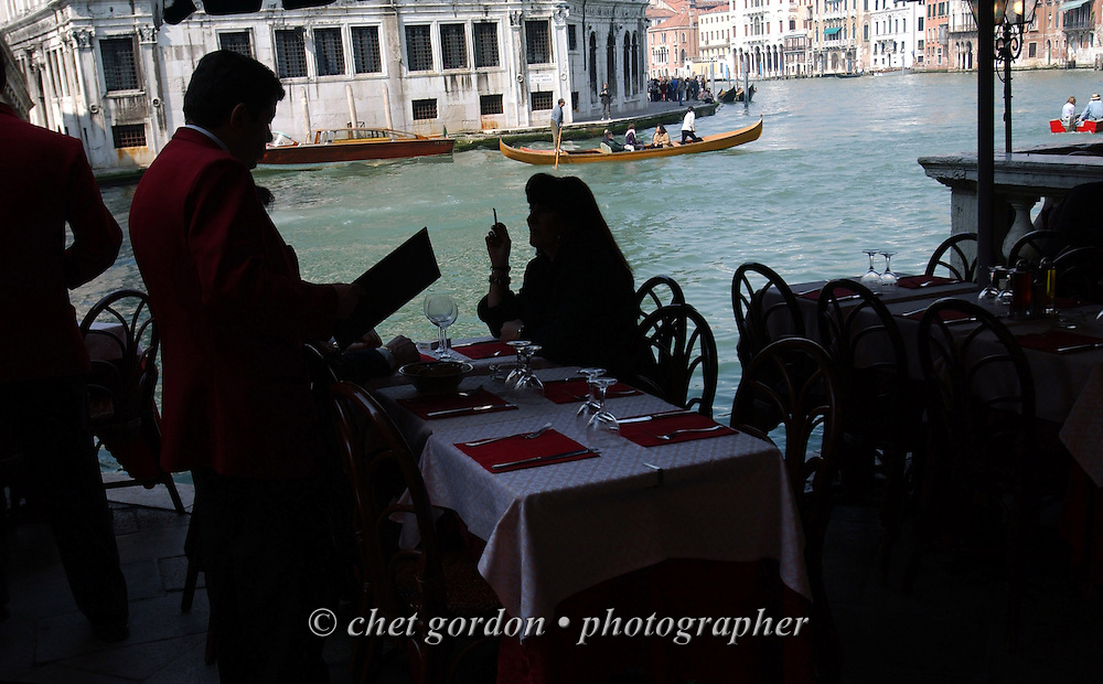 Lunching on the Grand Canal, near the Rialto Bridge, in Venice, Italy. April 2002.