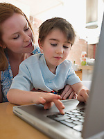 Mother Helping Son Use Laptop