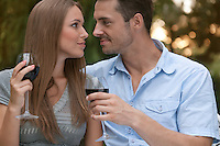 Loving young couple with red wine looking at each other in park