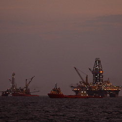 The Transocean Development Driller III and Helix Energy Solutions, Q4000 platform are seen near sunrise at the BP Plc Macondo well site in the Gulf of Mexico off the coast of Louisiana, U.S., on Friday, July 30, 2010. BP Plc continues to work on a relief well to permanently plug the source of the largest oil spill in U.S. history.  Photographer: Derick E. Hingle/Bloomberg