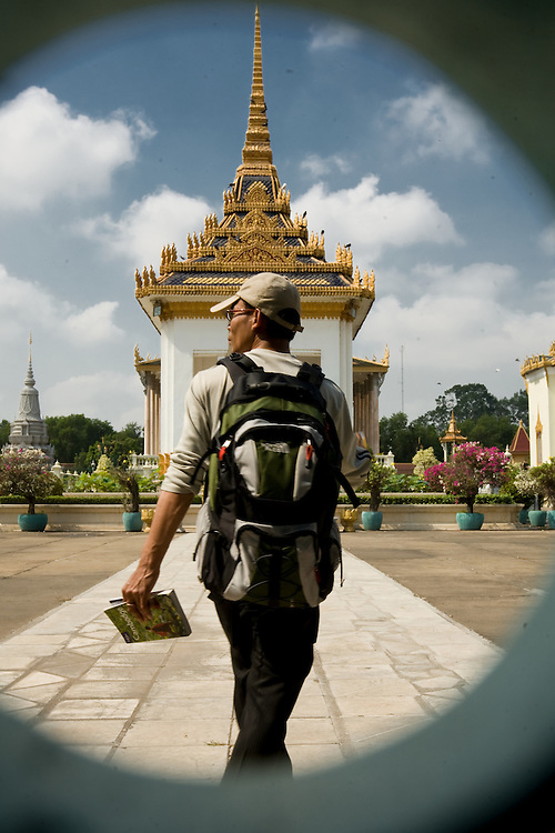 A male tourist, following the leads Lonely Planet, at the Royal Palace, Phnom Penh, Cambodia