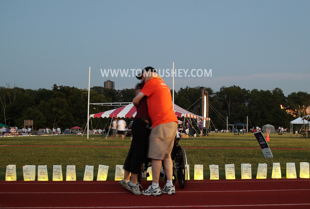 Goshen, New York - A man and a woman hug each other on the track, which is lined with luminaria in remembrance of cancer victims, during the Relay for Life at Goshen High School on June 19, 2011. The Relay for Life is the American Cancer Society's signature fundraising event. Participants celebrate the lives of people who have battled cancer, remember loved ones lost, and fight back against the disease by raising money.