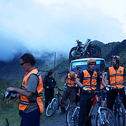 "Mountain Biking on Death Road, Bolivia...A tour group of Mountain Bikers stop to rest and be briefed about the next stage of the journey by their tour leader, biking down infamous narrow dirt road, most of the road no wider than 3.2 meter's, is cut into the side of the mountain with sheer drops to the left of up to 600 meter's with virtually no safety rails on the winding steep decent...The North Yugas Road is a 64 Kilometer road leading from La Paz to Corioico. It is legendary for it's extreme danger and in 1995 the Inter American Development Bank christened is as the ""world's most dangerous road"".. The road was built in the 1930's during the Chaco War by Paraguayan prisoners to connect the Amazon rainforest region of Northern Bolivia to it's capital City La Paz. One estimate is that 200 to 300 travelers were killed yearly along the road. On 24 July 1983, a bus veered off the Yungas Road and into a canyon, killing more than 100 passengers in what is said to be Bolivia's worst road accident..A new stretch of the La Paz-Coroico highroad was opened in 2006 to bypass the notorious stretch known as death road..The danger of the road has now made it a popular tourist destination starting in the 1990's and drawing thrill-seekers and mountain bike enthusiasts who ride on the 64km mainly downhill stretch from La Cumbre, a 4,700 meter peak to Yolosa, a decent of 3600 meter's (11,800 feet). The journey includes breathtaking views of snow covered peaks and towering cliffs and starts along modern asphalted road before entering the jungle itself and the most dangerous and notorious part of the ride. The infamous narrow dirt road, most of the road no wider than 3.2 meter's, is cut into the side of the mountain with sheer drops to the left of up to 600 meter's with virtually no safety rails on the winding steep decent..There are now many tour operators catering to this activity, providing information, guides, transport and equipment. Nevertheless, the Yungas Road remains dangerous"