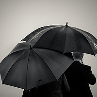 Two people with umbrellas huddling in the rain