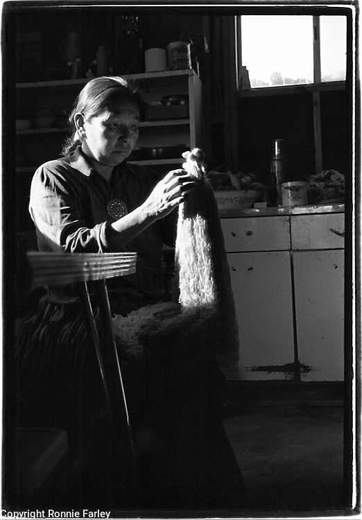 Mae Tso cleans wool from her sheep for rug weaving at her home in Big Mountain on the Navajo Reservation in Arizona, 1986