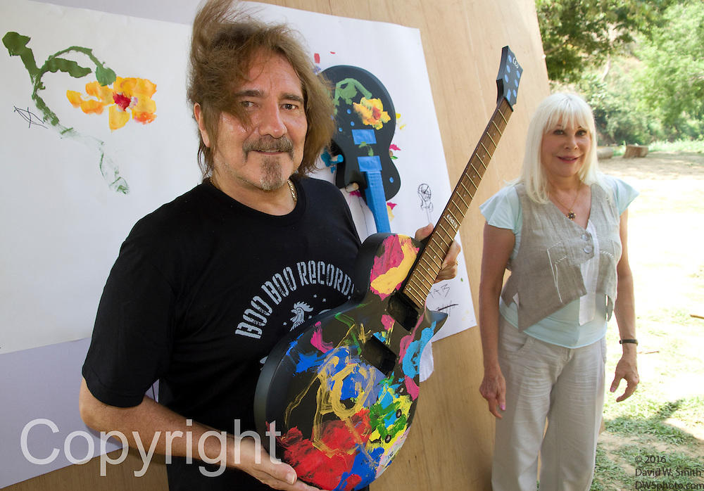 "Former Black Sabbath bassist and lyricist Terry ""Geezer"" Butler and  Wendy Dio, former wife of legendary Black Sabbath  guitarist Ronny Dio pose with guitars painted by Jaab, an elephant at the Elephant Life Experience (ELE) north of Chiang Mai during a press conference  at the camp as part of a joint effort to raise funds for cancer research and elephant conservation. The elephants at the camp will paint guitars by famous musicians, which will then be sold at a New York auction house. Ronny Dio died last year from stomach cancer and so his widow Wendy is raising money in an appeal called the ""Stand Up and Shout Cancer Fund."""