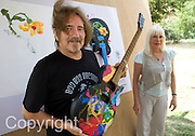 """Former Black Sabbath bassist and lyricist Terry """"Geezer"""" Butler and  Wendy Dio, former wife of legendary Black Sabbath  guitarist Ronny Dio pose with guitars painted by Jaab, an elephant at the Elephant Life Experience (ELE) north of Chiang Mai during a press conference  at the camp as part of a joint effort to raise funds for cancer research and elephant conservation. The elephants at the camp will paint guitars by famous musicians, which will then be sold at a New York auction house. Ronny Dio died last year from stomach cancer and so his widow Wendy is raising money in an appeal called the """"Stand Up and Shout Cancer Fund."""""""