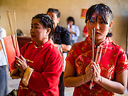 27 JANUARY 2017 - BANGKOK, THAILAND: Women pray on Chinese New Year at Wat Mangkon Kamalawat on Chinese New Year in Bangkok. 2017 is the Year of the Rooster in the Chinese zodiac. This year's Lunar New Year festivities in Bangkok were toned down because many people are still mourning the death Bhumibol Adulyadej, the Late King of Thailand, who died on Oct 13, 2016. Chinese New Year is widely celebrated in Thailand, because ethnic Chinese are about 15% of the Thai population. Wat Mangkon Kamalawat is a Thai-Chinese Buddhist temple.       PHOTO BY JACK KURTZ