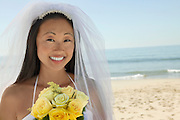Bride with bouquet on beach (close-up) (portrait)