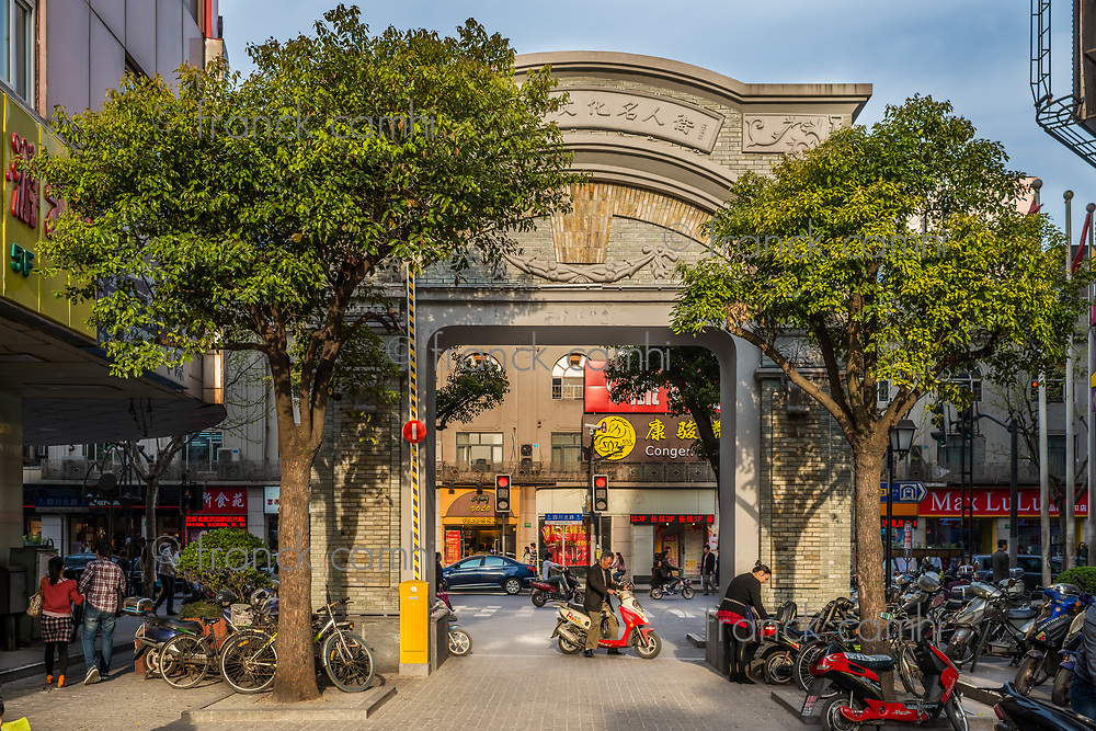 Shanghai, China - April 7, 2013: people parking scooter at historic entrance gate of the pedestrian way of duolon road at the city of Shanghai in China on april 7th, 2013